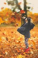 mooi klein meisje dat gele herfstbladeren in de lucht gooit in het park, herfstachtergrond met kopieerruimte foto