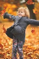 mooi klein meisje dat gele herfstbladeren in de lucht gooit in de herfstachtergrond van het park foto