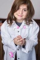 mooi klein meisje houdt een speelgoedstethoscoop vast en speelt een dokter foto