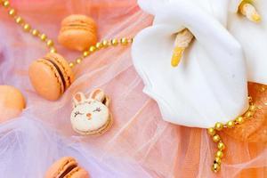 oranje bitterkoekjes met chocolade vulling en paashaas bitterkoekjes, op oranje tule achtergrond foto
