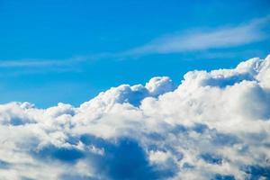 pluizige witte wolken op een blauwe lucht. het uitzicht vanuit het raam van het vliegtuig. achtergrond voor ontwerp. foto