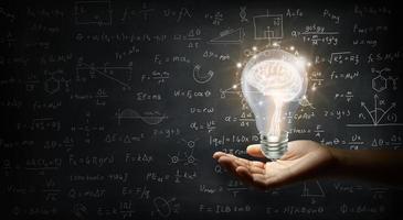 hand met een brein in een gloeilamp op het schoolbord aan de muur foto