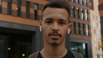 portret van een jonge man met draadloze oordopjes foto