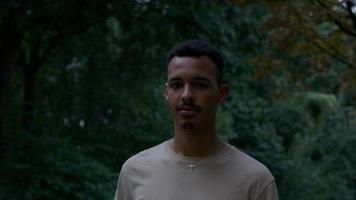 portret van een jonge man die in het park loopt en naar de camera kijkt foto