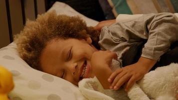 jonge jongen wordt naar bed met zacht stuk speelgoed voor het slapengaan foto
