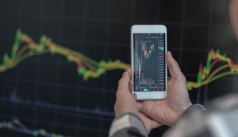 zakenman handelaar investeerder analist met behulp van mobiele telefoon app analytics voor cryptocurrency financiële beurs analyse analyseer grafiek handelsgegevens index investeringsgroei grafiek op smartphone scherm. foto