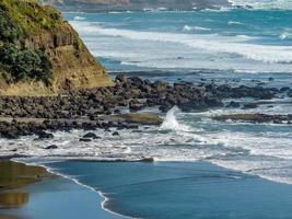 golven slaan aan wal op muriwai beach, auckland, nieuw-zeeland foto