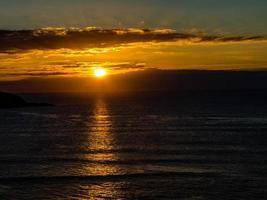 ondergaande zon op muriwai beach, auckland, nieuw-zeeland ze foto