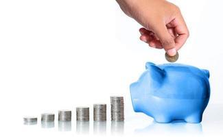 het concept om geld te besparen, hand die een muntstuk in spaarvarken op witte achtergrond zet foto
