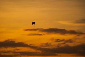 het silhouet van de paramotor bij zonsondergang foto