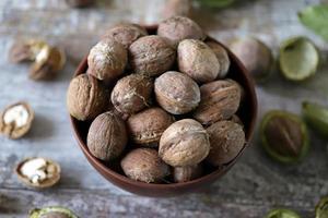 walnoten in een kom. walnootblaadjes walnoten in een groene schil foto