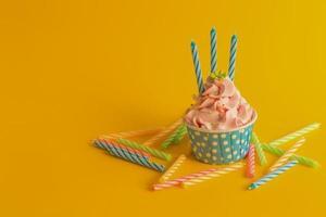 smakelijke verjaardag cupcake met kaarsen op gele kleur achtergrond foto