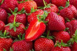 rijpe rode aardbeien op aardbeienachtergrond foto