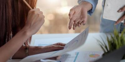 close-up zakenmensen die de grafieken en grafieken bespreken die de resultaten van hun succesvolle teamwerk laten zien foto