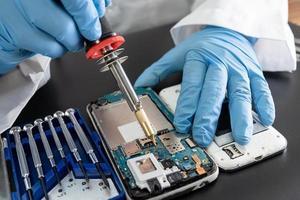 technicus die binnenkant van mobiele telefoon repareert door soldeerbout. geïntegreerde schakeling. het concept van gegevens, hardware, technologie. foto
