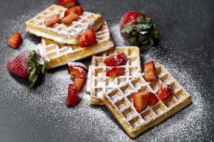 belgische wafels met aardbeien en suikerpoeder op zwarte bordachtergrond. foto