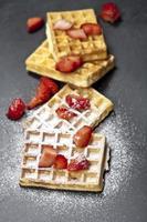 belgische wafels met aardbeien en suikerpoeder op zwart bord. foto