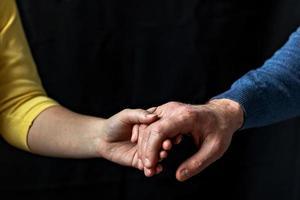 jong stel hand in hand met liefde en zorg, man en vrouw zijn teder dicht bij elkaar en tonen steun en begrip foto