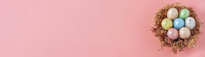 paaseieren in een natuurlijk nest met mos op een roze achtergrond. uitzicht van boven. banier foto