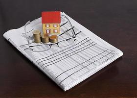 papieren huis met muntenstapel en bril op krantenpapier foto