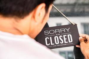 aziaten met bord open en gesloten in restaurant voor lockdown-ideeën ontgrendelen vrijheid toeristisch reizen voor levensstijl klantenbord open en gesloten welkom nieuwe normol tijdens coronavirusziekte covid-19 ontgrendelen lockdown foto