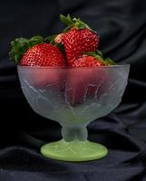 kopje rijpe aardbeien op zwarte achtergrond foto