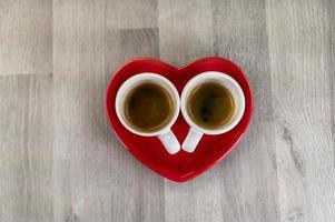 twee kleine kopjes koffie met een hartschotel foto