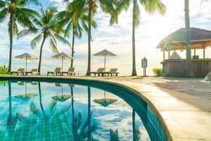 mooie luxe parasol en stoel rond buitenzwembad in hotel en resort met kokospalm op zonsondergang of zonsopgang foto