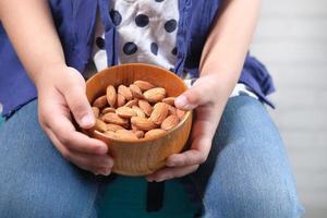 close-up kind meisje hand met een kom op amandel foto