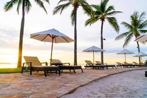 parasol en stoel rond zwembad in hotelresort met zonsopgang in de ochtend foto