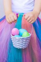 klein meisje in tutu-rok, met kleurrijk paasei in de mand foto