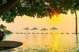 parasol en stoel rond zwembad met zeezicht op zee foto