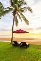 paraplu met stoel met zee strand achtergrond en zonsopgang in de ochtend foto