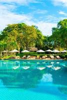 mooie luxe parasol en stoel rond buitenzwembad in hotel en resort met kokospalm op blauwe hemel foto