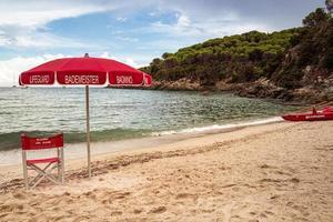 fetovaia, eiland elba, toscane italië 22 september 2020 badmeesterstoel en parasol op het lege strand van fetovaia, eiland elba, toscane, italië reddings- en veiligheidsconcept voor zwemmers foto