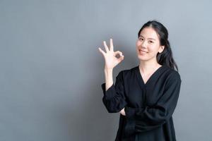 jonge aziatische vrouw die lacht en een goed teken toont foto