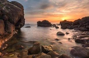 rotsachtig strand bij zonsondergang foto