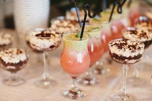 zomer koude cocktails met een badkuip. limonade water. verschillende limonades met ijsblokjes en schijfjes citroen in mason jar staan op een houten tafel foto
