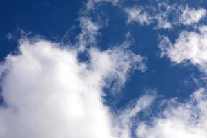 blauwe hemelachtergrond met wolken. opklaringen en mooi weer. selectieve focus foto