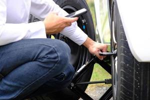 aziatische jonge man zittend op een kapotte auto die om hulp roept en wielvoertuigen op de weg repareert, ter vervanging van winter- en zomerbanden. seizoensgebonden bandenvervangingsconcept foto