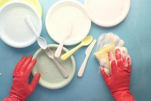 spons, rubberen handschoenen en kleurrijke plaat op blauw foto