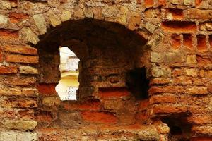oude oude ruïnes van een oud bakstenen gebouw met een klein raam foto