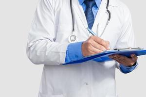 arts in laboratoriumjas houden en schrijven van patiëntendossier of medische notities op zoek, geïsoleerd op een witte achtergrond foto