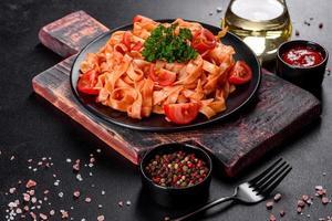 heerlijke verse pasta met tomatensaus met specerijen en kruiden op een donkere achtergrond foto