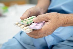 Aziatische senior of oudere oude dame vrouw patiënt met antibiotica capsule pillen in blisterverpakking voor behandeling infectie patiënt in ziekenhuis apotheek drogisterij concept. foto