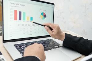 aziatisch accountantstype toetsenbord om informatie in te voeren, te werken, te berekenen en te analyseren, rapportgrafiek, projectboekhouding met notebook in modern kantoor, financiën en bedrijfsconcept. foto