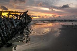 oude houten golfbrekerruïnes en zijn weerspiegeling op nat zandoppervlak bij zonsondergang foto