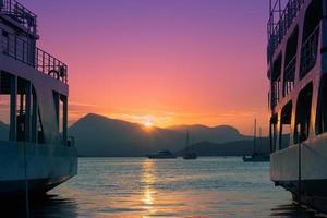 veerboten aangemeerd in de jachthaven, mooie roze lucht op de achtergrond zomer reizen achtergrond met kopie ruimte foto