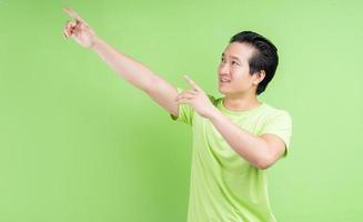 portret van een aziatische man in een groen t-shirt die zich voordeed op een groene achtergrond foto