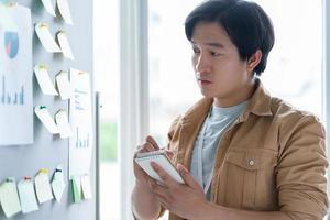 Aziatische zakenman die een bedrijf plant foto
